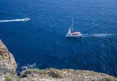 Catamaran and motor boat from cliff at Akrotiri Royalty Free Stock Photos