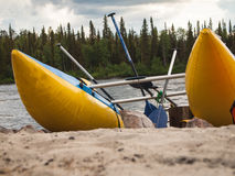 Catamaran with oars standing on sand. On forest background Stock Photos