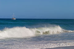 A catamaran off the coast of Kauai with a big wave in the foreground royalty free stock image