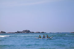 A catamaran paddles on the waves Stock Photography