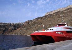 Catamaran in the Port. Red catamaran in the port of the town of Thira on Santorini archipelago Royalty Free Stock Photos