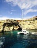 Catamaran przy kotwicą pod falezami Comino zdjęcie stock