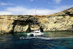 Catamaran przy kotwicą pod falezami Comino obraz stock