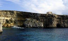 Catamaran przy kotwicą pod falezami Comino obrazy royalty free