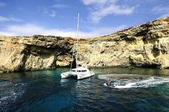 Catamaran przy kotwicą pod falezami Comino fotografia stock
