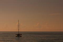 Catamaran sailboat on a calm sea at sunset. Catamaran sailboat on a calm sea at orange sunset Royalty Free Stock Photography