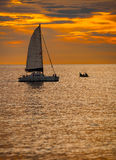 Catamaran Sailboat on a Tropical Sea at Sunset. Sky blazing with the last orange light of sunset over a catamaran sailboat, with its sail unfurled, on a tropical Royalty Free Stock Photography