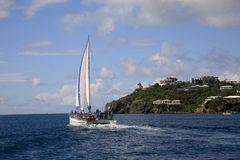 Catamaran Sailing past St. Thomas. A catamaran is sailing past a villa covered tip of the isalnd of St. Thomas. The boat is loaded with tourists who are heading Royalty Free Stock Images