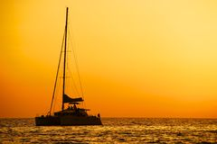 Catamaran sailing at sunset Stock Photos