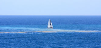 Catamaran sails through pollution in the ocean Royalty Free Stock Images