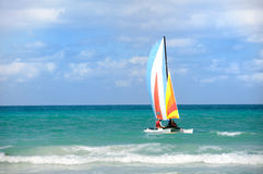 Catamaran on the sea. A catamaran with colorful sails floating on the turquoise see Royalty Free Stock Image