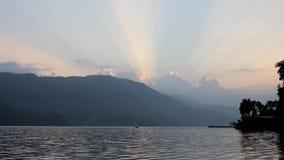 Catamaran sur le lac le soir contre le contexte des montagnes et les rayons du soleil dans le ciel de coucher du soleil clips vidéos