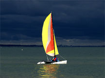 Catamaran in Thunderstorm. Bright Sunlight before Black Clouds in advancing Storm Stock Image
