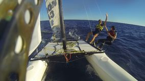Catamaran under sail at high speed, people aside the hull high-fiving each other. Stock footage stock video footage