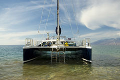Catamaran, West Maui Mountains in background. Hawaii. Catamaran in shallow water off beach, West Maui Mountains in background. Maui Hawaii royalty free stock image