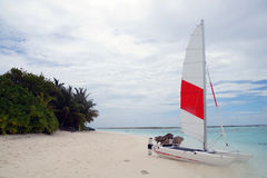 A catamaran with a white and red sail on the beach. The Maldives in October, indian ocean, Ari Atoll Stock Photo
