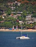Catamaran In Zihuatanejo. This is an image of a catamaran in the Bay of Zihuatanejo.  In the background people can be seen relaxing and enjoying La Ropa beach Stock Photo