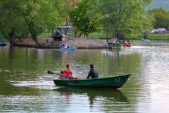 Catamaranes y barcos con la gente en el lago Imagen de archivo libre de regalías