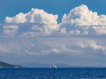 Catamarano dell'yacht sui precedenti delle nuvole sull'isola di Kefalonia nel Mar Ionio in Grecia fotografie stock libere da diritti