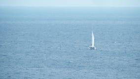 Catamarano distante di navigazione in mare fotografia stock