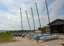 Catamarans on beach. Row of catamaran boats on beach with sea in background Stock Photography