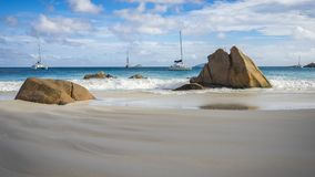 Catamarans behind granite rocks on seychelles beach. Multiple catamarans behind golden granite rocks in the white sand on seychelles beach Royalty Free Stock Photos
