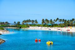 Catamarans on blue water beach. Nassau, Bahamas- March 09, 2016: summer beach with catamarans in water and people on vacation with blue sky and green palms on Royalty Free Stock Image