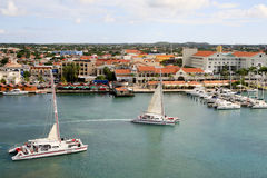 Catamarans Leaving the Oranjestad harbor. Two catamarans full of tourists are leaving the inner Oranjestad harbour. One has its sail up, the other is in the Stock Images