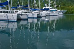 Catamarans at marina. A view across clear blue water to several large catamarans docked at the Nanny Cay Marina on the Tortola Island of the British Virgin Royalty Free Stock Photo