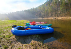 Catamarans and rubber boat on river bank Royalty Free Stock Photos