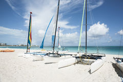 Catamarans on tropical beach. Catamarans pulled up on Caribbean beach under interesting cumulus humilis cloud formation Royalty Free Stock Images