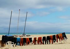 Catamarans and wetsuits on the beach. Colorful wetsuits at a clothing line on the beach of Parque Natural de las Dunas de Corralejo. This park is a nature area Stock Photography