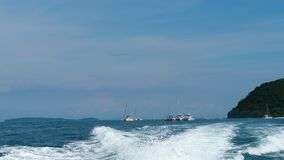 Catamarans, yachts and speedboats in Andaman sea. View from the rear of moving speedboat stock video footage