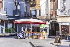 """Catanië, Sicilië, Italië †""""16 augustus, 2018: een mens op een autoped koopt fruit van een straatventer royalty-vrije stock afbeelding"""