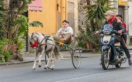 Catania Italy - 01 13 2019: A boy is riding a cart with a white little horse and children are riding a motorcycle on the street stock photography