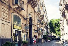 """Catania Sicilien, Italien †""""august 8, 2018: den unga mannen och kvinnan kysser på ingången till hotellet i gammal byggnad på royaltyfri foto"""