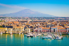 Catania Sicily, Italy. City and harbor view of Catania port, Sicily, Italy. Boats and yachts in port, city with beautiful buildings and smoking vulcano Etna in royalty free stock photography