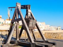 Catapulta antigua en las paredes de la ciudad de Alghero En el fondo una vista de la ciudad Foto de archivo