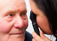 Cataracts. Optician checking elderly patient's cataracts with optical device Royalty Free Stock Image