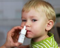 Catarrh - nose drops, nasal spray. Mother spraying 2 years old baby boy medicine in nose, nose drops, nose spray Stock Photo