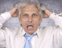 Catastrophe. Angry senior businessman on silver background Stock Photography