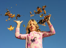 Catch. A girl throws leaves up into the air Stock Photo