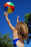 Catch the ball. Young girl with beach ball and blue sky Stock Images