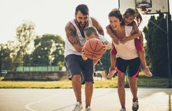 Catch the ball and go into the game. Family playing basketball stock images