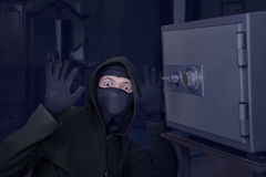 Catch the burglar concept. Thief with balaclava caught in front a safe Stock Image