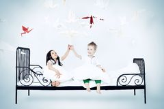 Catch a dream. Cute kids sitting together on the bed under the blanket. Dream world Stock Photos