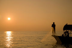 Catch fish with net at sunrise Stock Images