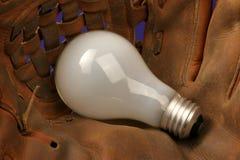 Catch an Idea. Catcher's mitt with a light bulb Royalty Free Stock Photo