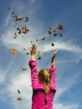 Catch the leaves. A young girl throwing leaves up into the air and catching them Royalty Free Stock Image