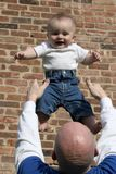 Catch Me Daddy_1. A father throwing his son up in the air and catching him stock images